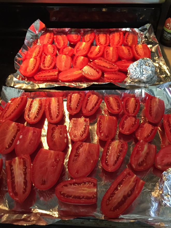 Cut the tops off of the tomatoes and then slice them in half.